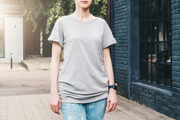 Summer day. Front view. Young millennial woman dressed in gray t-shirt is stands on city street. Mock up. Space for logo, text, image. Instagram filter, film effect, bokeh effect.