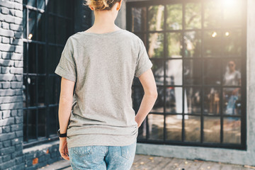 Summer day. Back view. Young millennial woman dressed in gray t-shirt is stands on city street. Mock up. Space for logo, text, image. Instagram filter, film effect, bokeh effect.