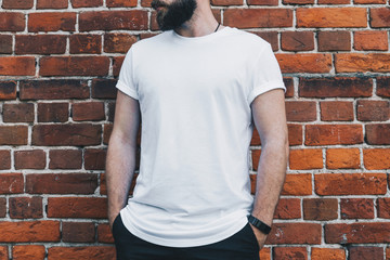 Summer day. Front view. Young bearded millennial man dressed in white t-shirt is stands against dark brick wall. Mock up. Space for logo, text, image. Instagram filter, film effect, bokeh effect.