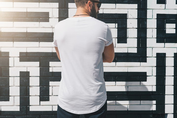 Summer day. Back view. Young bearded millennial man dressed in white t-shirt is stands against brick wall. Mock up. Space for logo, text, image. Instagram filter, film effect, bokeh effect.