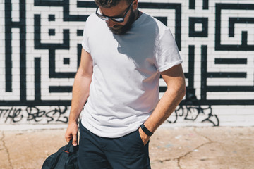 Summer day. Front view. Young bearded millennial man dressed in white t-shirt and sunglasses is stands against brick wall. Mock up. Space for logo, text, image. Instagram filter, film effect, bokeh