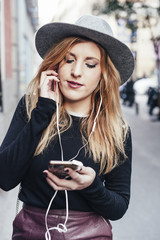 Young blonde woman listening music with earphones of her mobile phone in Madrid streets, Spain