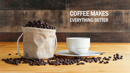 "Inspirational positive quote "" Coffee makes everything better"" with hot coffee and roasted coffee bean in heart shape on the wooden desk."