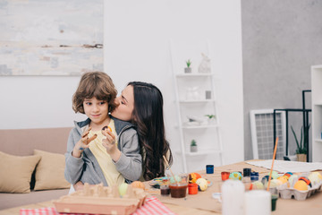 mother kissing her son while he painting easter eggs