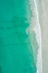 aerial view of clean white sandy beach with tropical turquoise waters