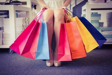 Woman trying on court shoes with many shopping bags
