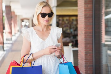 Pretty blonde on the phone with shopping bags