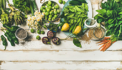 Spring healthy vegan food cooking ingredients. Flat-lay of vegetables, fruit, seeds, sprouts, flowers, greens over white wooden background, top view, copy space. Clean eating, diet food concept