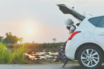 Beautiful sunset sky and clouds while young woman traveler sitting on the white hatchback car....