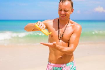 Man using sunscreen cream on bright sunny day