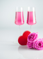 Romantic scenery with  red heart-shaped box , rose flowers and two glasses of pink champagne