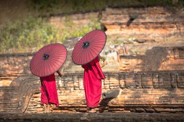 Two novices spread a red umbrella