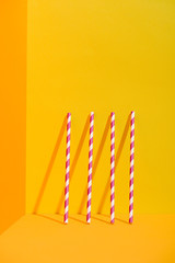white and red striped straws standing at orange wall