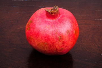 Pomegranate fruit  over wood  grain  background . Healthy eating concept.