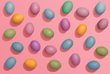 Multi colored Easter eggs on pink background, fun Easter flat lay