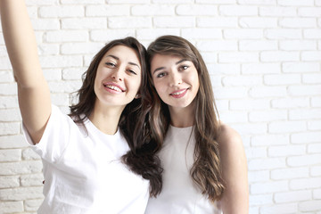 Portrait of two millennial females, fooling around in front of mobile smartphone camera. Brown eyed model girls with long brunette wavy hair and beautiful smiles in white blank shirt.