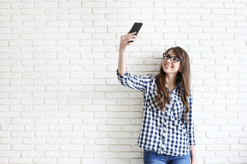 Stylish woman making selfie with shopping bag on the yellow wall background. Winter holiday sale