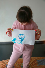 Cute little girl with painting. Isolated on grey background.