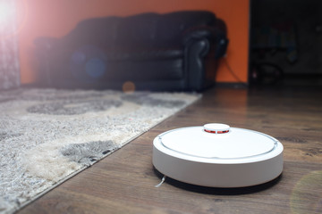 Home vacuum cleaning robot in action on genuine living room wooden floor.