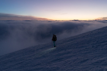 Hiking woman with headlamp on snow in Slovak mountains above clouds after sunset in winter