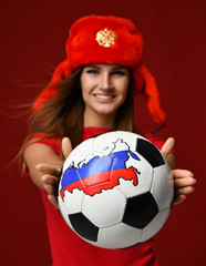 Russian style fan sport woman player in red uniform give soccer ball celebrating happy smiling