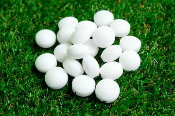 White naphthalene balls on grass background