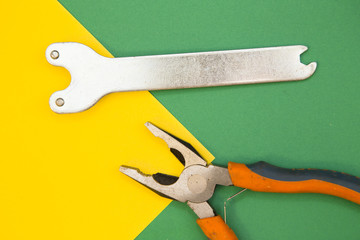 Home, House Repair, Redecorating, Renovating Concept. Pliers and a wrench on green and yellow background with copy space, top view, flat lay