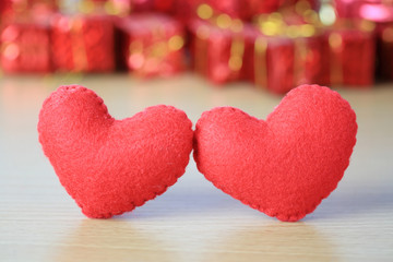 red heart placed on a wooden floor on red gift box of blur background.