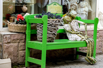 Flower shop. On the bench sit two frogs