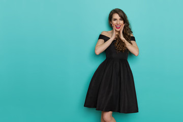 Elegant Woman In Black Cocktail Dress Is Holding Head In Hands And Laughing