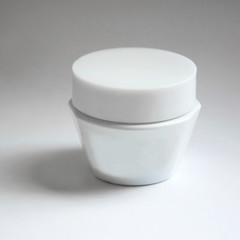 White jar for cream. The container for the cosmetic oils and creams.