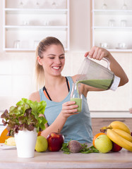 Girl pouring smoothie in bottle in kitchen