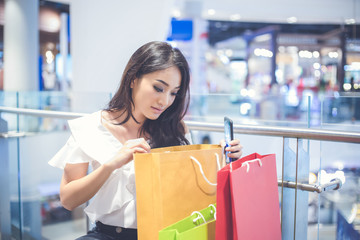 Asian women and Beautiful girl is holding shopping bags and using a smart phone and smiling while doing shopping in the supermarket/mall