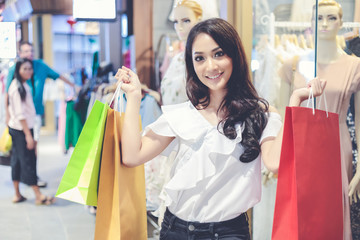 Asian women and Beautiful girl is holding shopping bags smiling while doing shopping in the supermarket/mall
