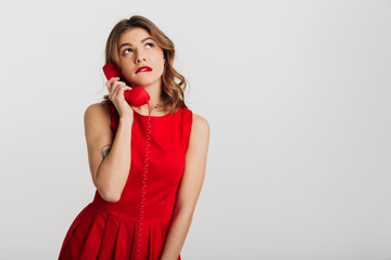 Portrait of a pensive young woman dressed in red dress