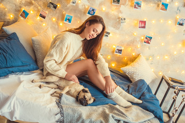 Young woman weekend at home decorated bedroom touching dog