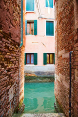 The end of a narrow alley in Venice leading to a canal with windows on the opposite side.