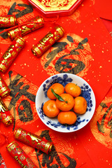 Chinese new year oranges in bowl and fake firecrackers on spring festival  couplets that says happiness and spring is coming
