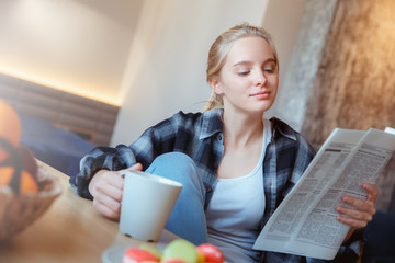 Young woman at home in the kitchen drinking tea reading news