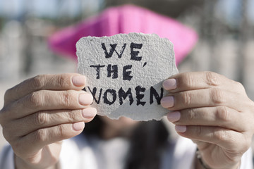 woman with a pussyhat and the text we the women