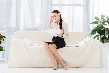 concentrated businesswoman doing paperwork while sitting on sofa in office