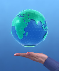 World Globe. 'Holographic' CG model of a globe above the facing up palm of a men's hand on blue background. Photo and 3D-render compositing.