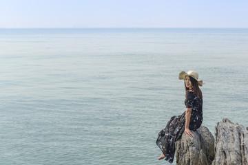 Beautiful woman on rock in the sea.