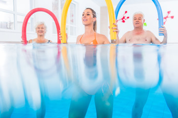 Group in water physical therapy training with pool noodles, shot half underwater