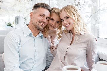 happy young family spending time together in cafe