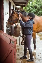 Pretty woman fixing saddle
