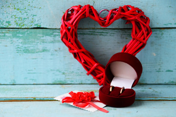 Background, texture on St. Valentine's day February 14: red heart, flowers and a red velvet box with two wedding rings on a blue wooden background, concept of love, wedding, engagement,
