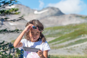 Little girl making pictures with smartphone on a mountain trail