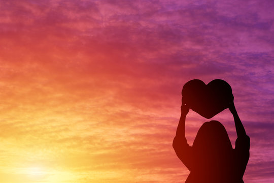 Silhouette of a woman holding a heart shape look at the sky sunset background