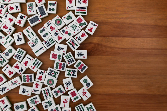 White-green tiles for mahjong on a brown wooden background. Empty place in the rigth.